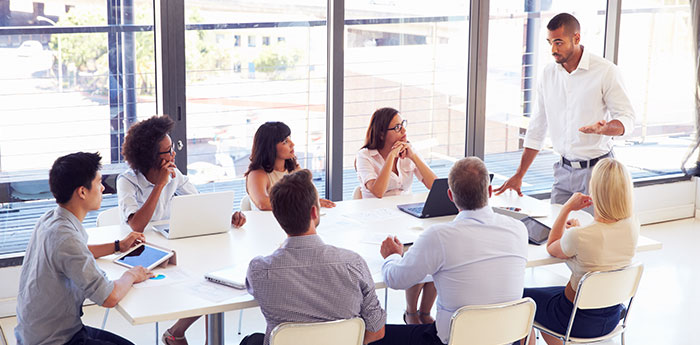Directors & Officers Liability Insurance: A team of people sitting at a table, looking up to their team leader.