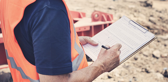 Products Liability Insurance: A man in a Hi Vis Jacket filling in a document on a clipboard.