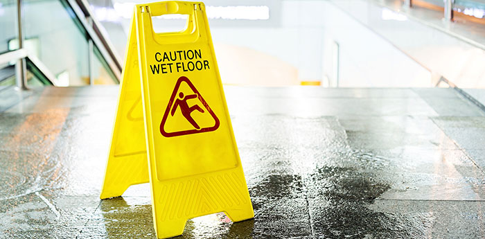 Public Liability Insurance: A yellow caution wet sign floor at the top of stairs.