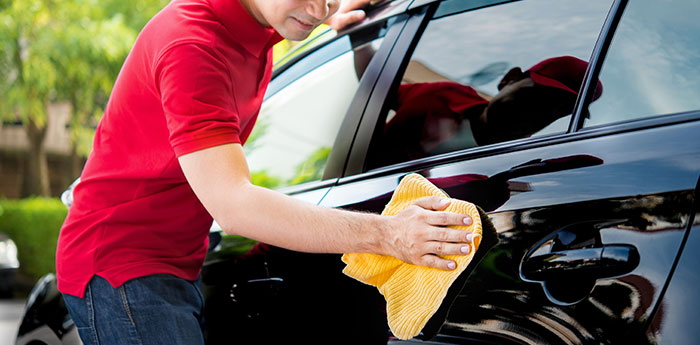Vehicle Detailing Insurance: A man in a red top drying down a black car.